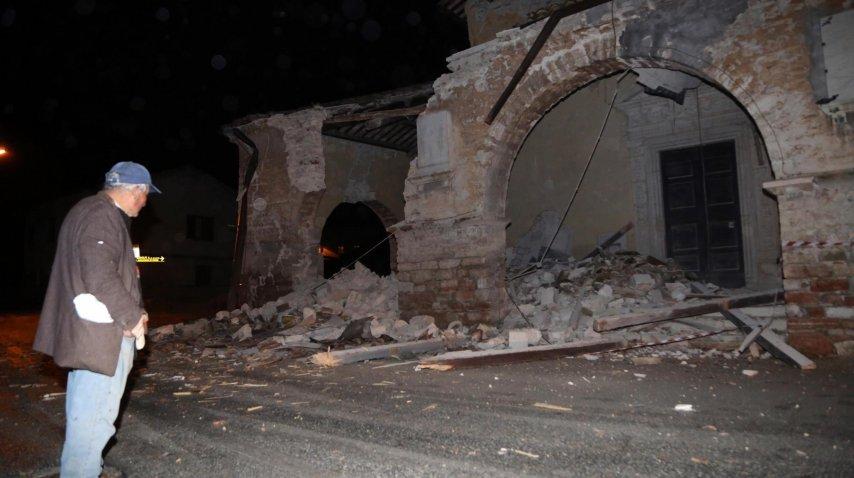 Un hombre mira lo que quedó de un edificio en la villa Sant'Antonio