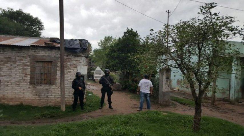 Policías llevando a cabo el allanamiento
