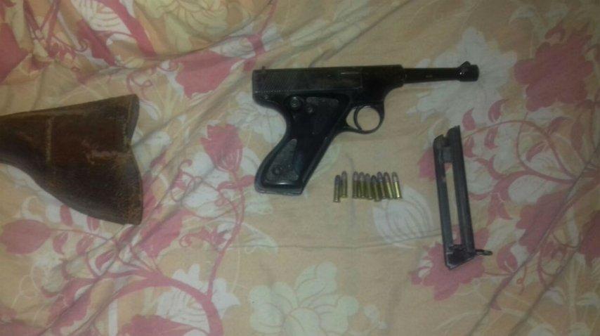 Una pistola que se encontró durante el allanamiento