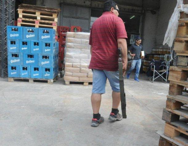 El custodio de Rodolfo Monetti deambula con su arma larga por la distribuidora<b><br></b>